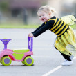 Happy blond little girl in bee costume pushing toy — Stock Photo #37672857
