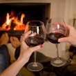 Couple drinking wine in front of a fire — Stock Photo #38314875