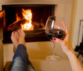 Woman drinking wine in front of fire — Stock Photo