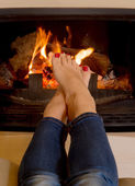 Woman's feet in front of a fire — Stock Photo