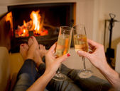 Couple drinking champagne in front of a fire — Stock Photo