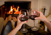 Couple drinking wine in front of a fire — Stock Photo