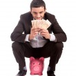 Happy business man sitting on piggy bank counting money euros — Stock Photo #38630159