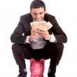 Happy business man sitting on piggy bank counting money euros — Stock Photo
