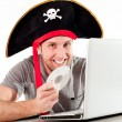 Min pirate hat downloading music on laptop — Stock Photo #39022315