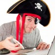 Stock Photo: Man in pirate hat downloading music on a laptop
