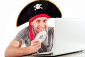 Man in pirate hat downloading music on a laptop — Stock Photo