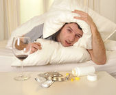 Man with headache and hangover in bed with tablets — Stock Photo