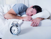 Young attractive man sleeping on bed — Stock Photo