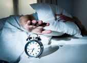 Sleeping man disturbed by alarm clock early morning — Stock Photo