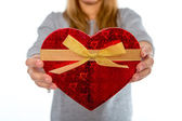 Woman holding a love heart box on white background — Stock Photo