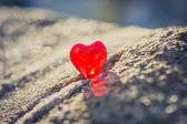 Macro red heart on a vintage cream wall — Stock Photo