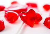 Macro red heart with chocolates and lollipops on white background — Foto Stock