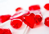 Macro red heart with chocolates and lollipops on white background — Φωτογραφία Αρχείου