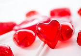 Macro red heart with chocolates and lollipops on white background — Stock Photo