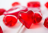 Macro red heart with chocolates and lollipops on white background — Stockfoto