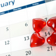 February calendar page and little red hearts marking valentines day — Stock Photo #39761151