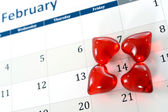 February calendar page and little red hearts marking valentines day — Stock Photo