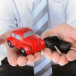 Macro red toy car with car keys in mans hand — Stock Photo