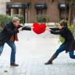 Stock Photo: Attractive couple fighting over love heart pillow