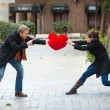 图库照片: Attractive couple fighting over love heart pillow
