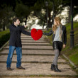 Attractive couple fighting over love heart pillow — Foto Stock #40626373