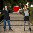 Attractive couple fighting over love heart pillow — Stock fotografie #40626649