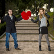 Attractive couple fighting over love heart pillow — Stockfoto #40626649