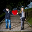 Attractive couple fighting over love heart pillow — Stock fotografie #40627845
