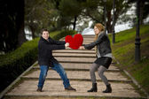 Attractive couple fighting over a love heart pillow — Stock Photo