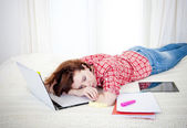Red haired student alseep on laptop while studing — Stock Photo