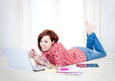 Happy red hair student, business woman lying down working on laptop — Stock Photo