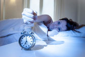 Close up alarm clock with red haired woman turning it off — Stock Photo