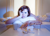 Red haired woman sick in bed with medicine — Stock Photo