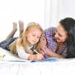 Young Mother and beautiful little daughter lying and drawing together — Stock Photo