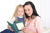Attractive woman with beautiful daughter reading book — Stock Photo
