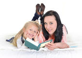 Attractive woman with adorable blond beautiful daughter reading book — Stock Photo