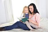有魅力的女人,与美丽的女儿看书 — 图库照片