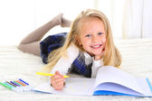 Adorable blond little girl on bed drawing with markers — Fotografia Stock