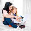 Happy mother and daughter working on computer sitting on bed together — Stock Photo