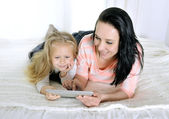 Happy young mother and little adorable blonde daughter with tablet — Stock Photo