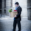 Frustrated business man on edgy street fired from job  carrying cardboard box looking desperate and in stress — Stock Photo #41583625