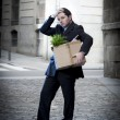 Frustrated business man on edgy street fired from job  carrying cardboard box looking desperate and in stress — Stock Photo #41583707