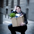 Frustrated business man on edgy street fired from job  carrying cardboard box looking desperate and in stress — Stock Photo #41583891