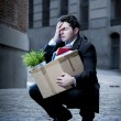 Frustrated business man on edgy street fired from job carrying cardboard box looking desperate and in stress — Stock Photo #41583935