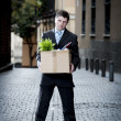 Frustrated business man on street fired carrying cardboard box — Stock Photo