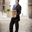 Frustrated business man on edgy street fired from job  carrying cardboard box looking desperate and in stress — Stock Photo #41584445