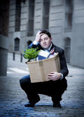 Frustrated business man on edgy street fired from job  carrying cardboard box looking desperate and in stress — Stock Photo
