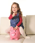 Happy Cute little girl sitting on huge piggy bank inserting Coin — Stock Photo