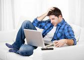 Uomo rilassato, utilizzando il computer a casa seduto sul divano — Foto Stock